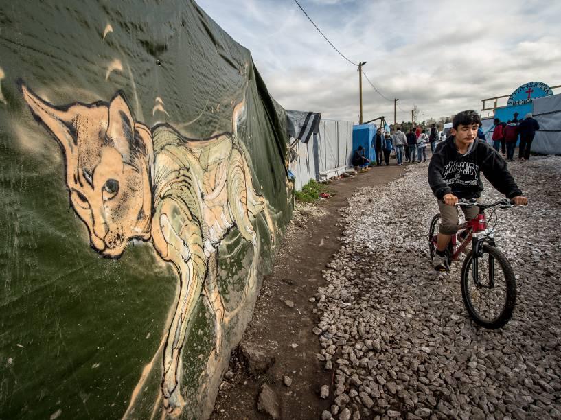 Jovem anda de bicicleta através do acampamento improvisado que abriga milhares de refugiados e é conhecido como Selva na cidade francesa de Calais -  29/10/2015