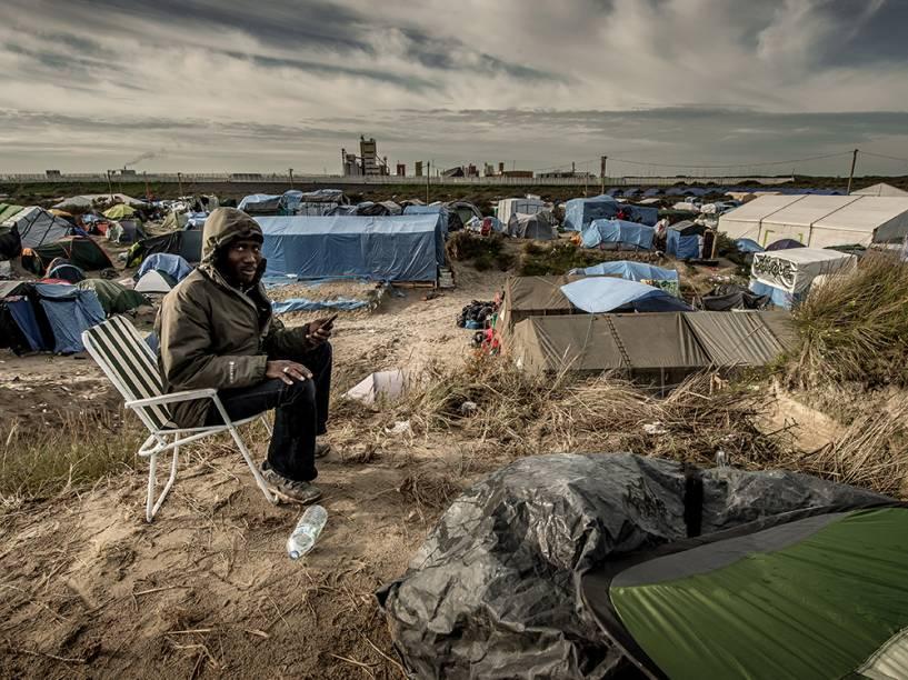 Homem usa um celular para ligar para sua família no Sudão. Ele vive no acampamento criado para imigrantes africanos em Calais, na França