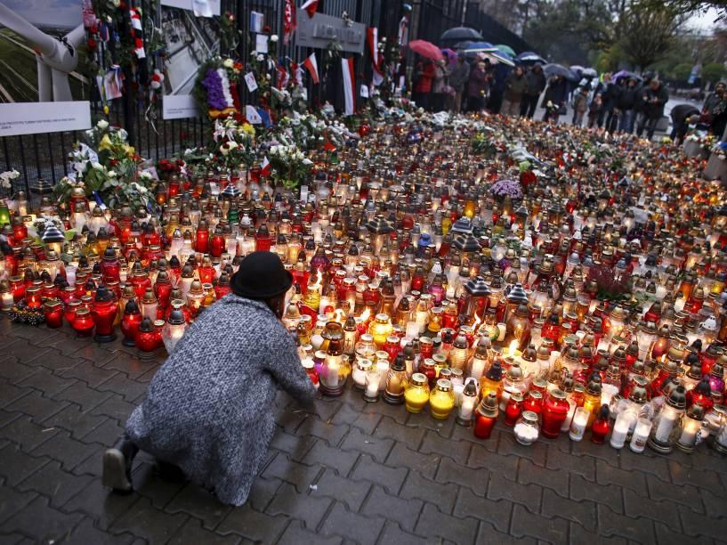 Em frente à embaixada francesa em Varsóvia, na Polônia, menina deixa um vela em homenagem às vítimas dos ataques terroristas em Paris - 16/11/2015