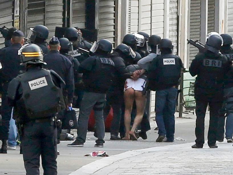 Um homem é levado por policiais durante operação em Saint-Denis, ao norte de Paris, nesta quarta-feira (18). Dois suspeitos morreram e outros sete foram presos na operação antiterrorista