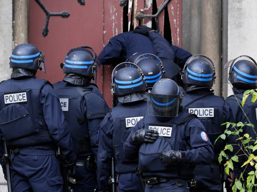 Policiais arrebentam porta de uma igreja em Sant-Denis, subúrbio de Paris, para manter a área segura durante caçada de suspeitos de ligação com os ataques terroristas - 18/11/2015