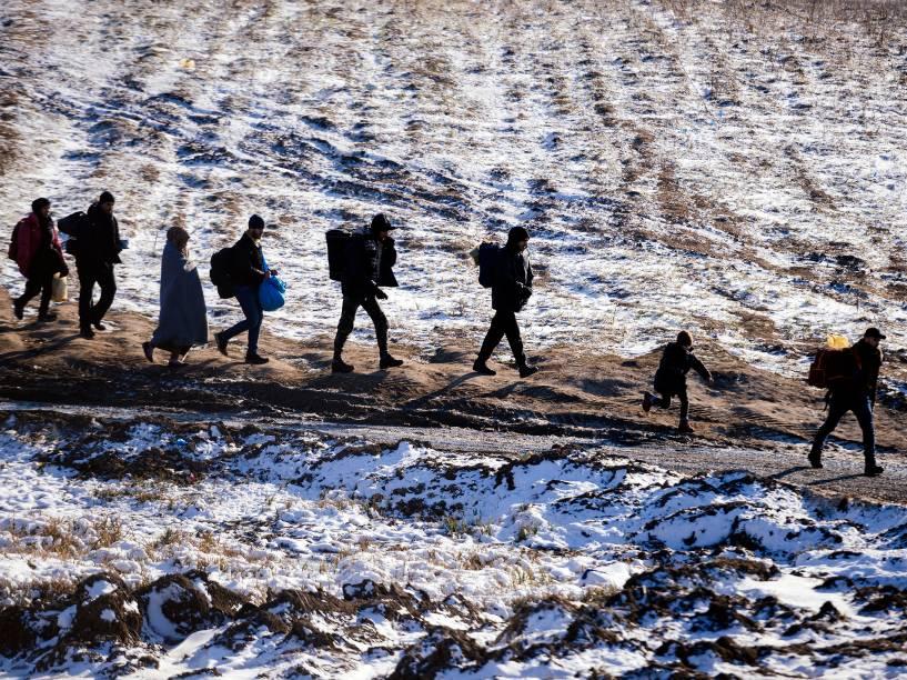 Refugiados caminham através de campos cobertos de neve através da fronteira entre a Macedônia e a Sérvia, próximo ao vilarejo de Miratovac, na Sérvia - 19/01/2016
