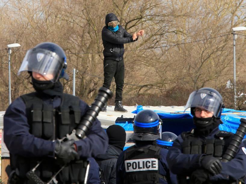 Policiais franceses guardam área enquanto um imigrante, ao fundo, ameaça cortar o pulso com uma faca sobre o teto de seu barraco durante operação para desfazer o campo de imigrantes que ficou conhecido como Selva, em Calais, no norte da França