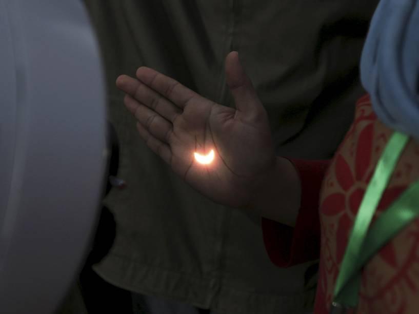 <p>Eclipse solar, que ocorreu hoje (9) na Indonésia, reflete na mão de pessoa através da lente de um telescópio</p>