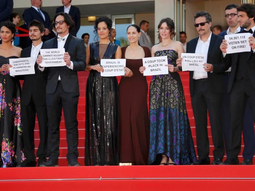 O diretor Kleber Mendonça Filho e o elenco do filme brasileiro Aquarius seguram cartazes em protesto contra o impeachment da presidente Dilma Rousseff no tapete vermelho do 69º Festival de Cinema de Cannes, na França - 17/05/2016