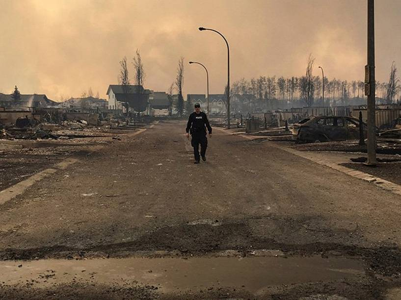 Policial observa os danos causados pelo incêndio florestal que atingiu a região da cidade de Fort McMurray, no Canadá. Cerca de 80 mil pessoas foram evacuadas do local - 05/05/2016