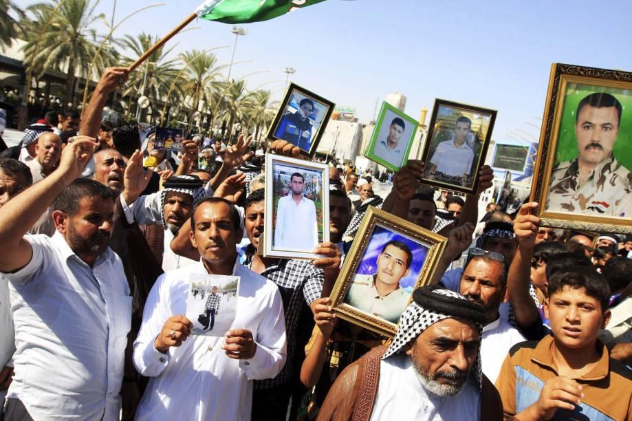 Cidadãos iraquianos protestam nas ruas de Kerbala, sul do Iraque, com fotos de parentes supostamente executados pelo Estado Islâmico