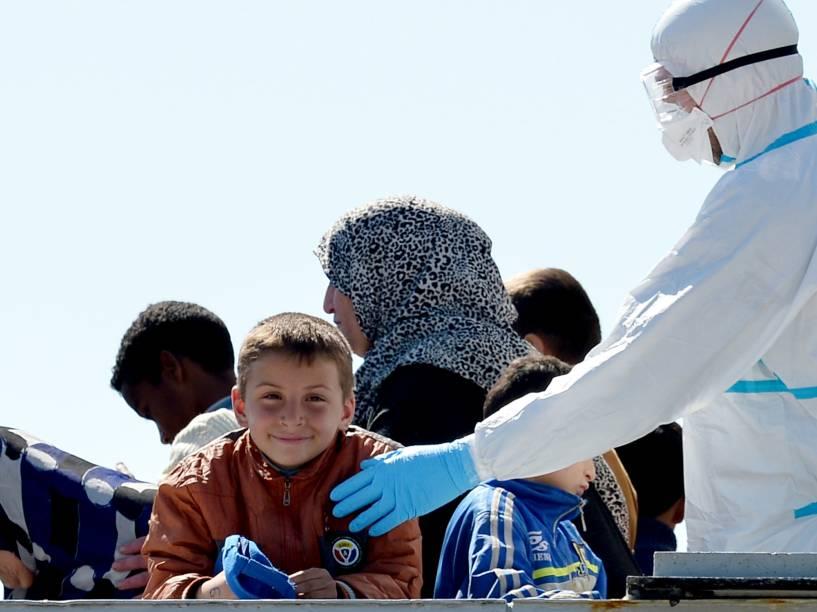 Oficial naval interage com menino que estava entre os imigrantes resgatados do navio com destino à Grécia