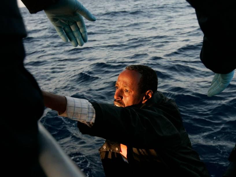 Vítima do naufrágio na costa da Líbia recebe ajuda para sair do mar. Cerca de 800 pessoas estavam a bordo quando o barco naufragou