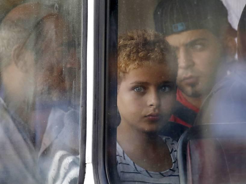 Garoto sírio vítima do naufrágio olha pela janela de um ônibus após chegar em uma base comunitária em Malta