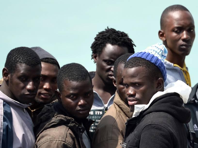 Imigrantes esperam equipe de resgate para desembarcar no porto siciliano em Catânia