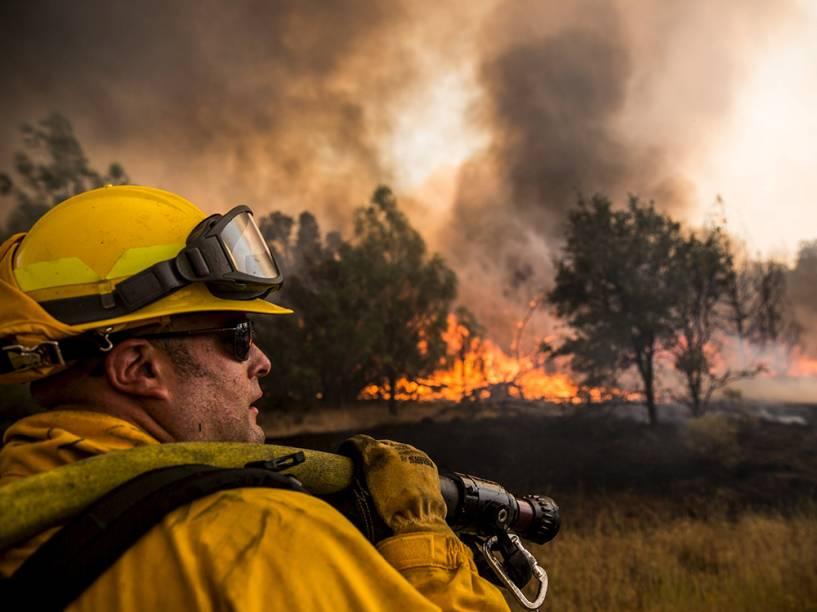 """Bombeiro tenta controlar as chamas do incêndio que ficou conhecido como """"Rocky Fire"""", em Clearlake, Califórnia"""