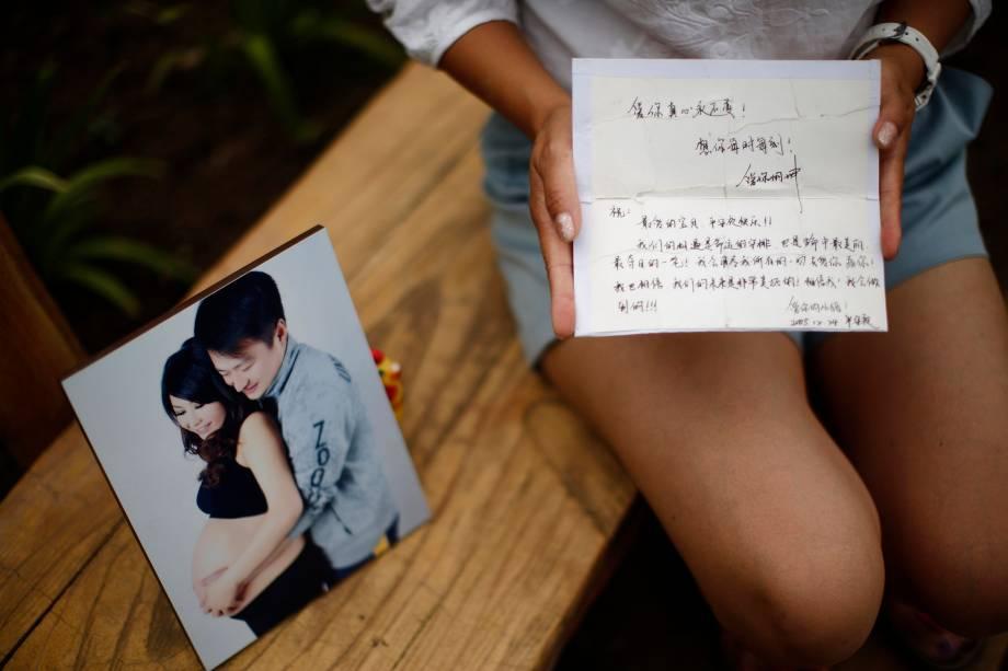 Cheng Liping, cujo marido Ju estava no vôo MH370 da Malaysia Airlines, mostra uma fotografia onde eles estão juntos e uma carta escrita por ele
