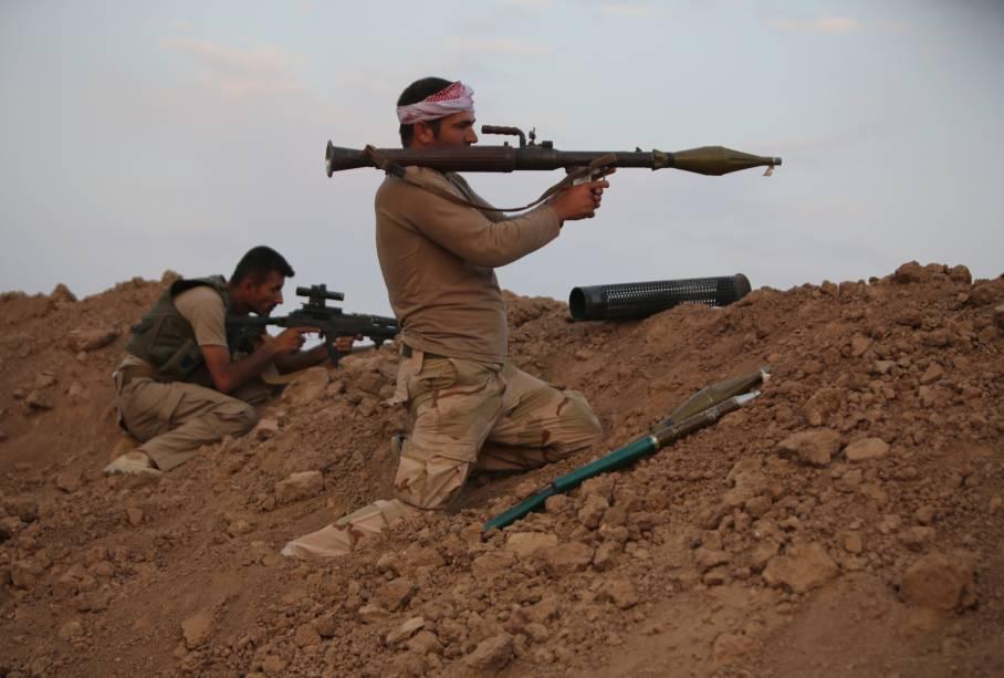 Soldado das forças curdas Peshmerga se prepara para lançar um foguete contra jihadistas, no Iraque
