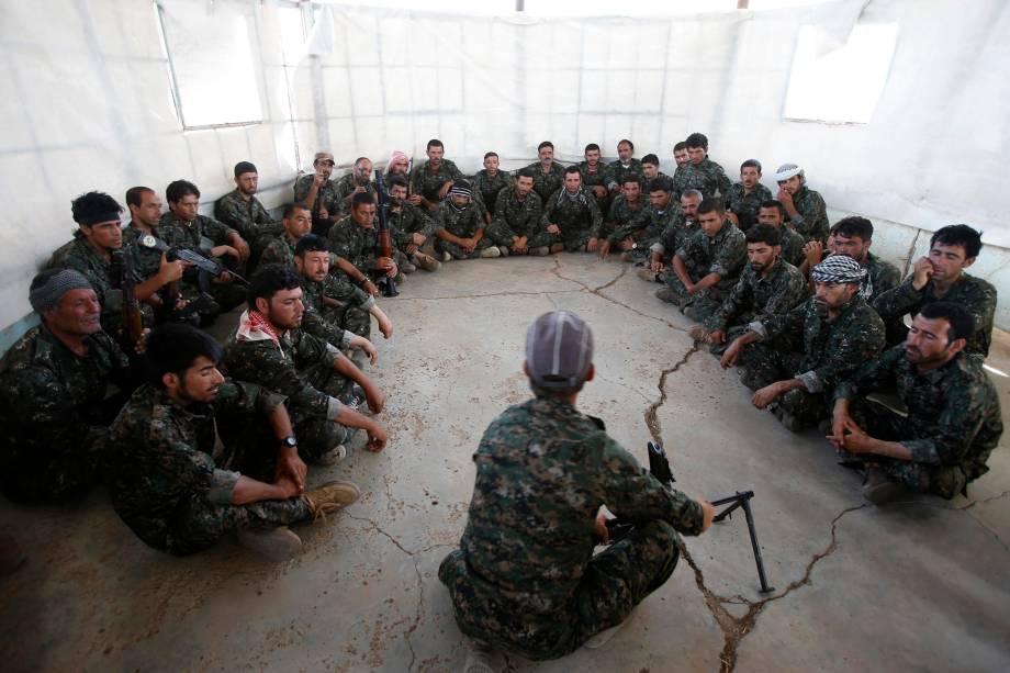 Voluntários yazidis durante instruções de como manusear armas para combater terroristas no Iraque