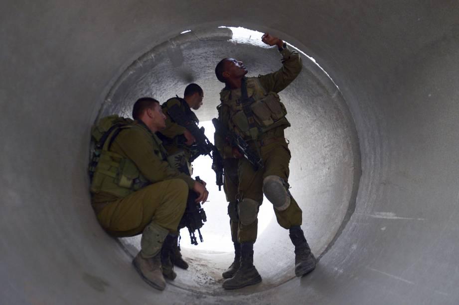 Soldados israelenses são fotografados enquanto se escondemem um cilindro de cimento,aos arredores da Faixa de Gaza, em 20/08/2014