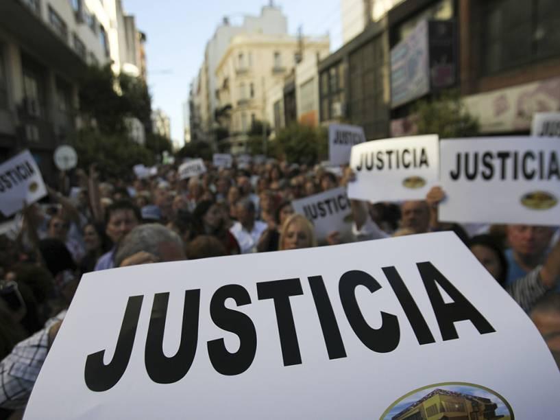 Dezenas de pessoas seguram cartazes durante uma manifestação nesta quarta-feira (21) para exigir justiça após a morte do promotor argentino Alberto Nisman, em frente à sede da Associação Mutual Israelita Argentina, em Buenos Aires