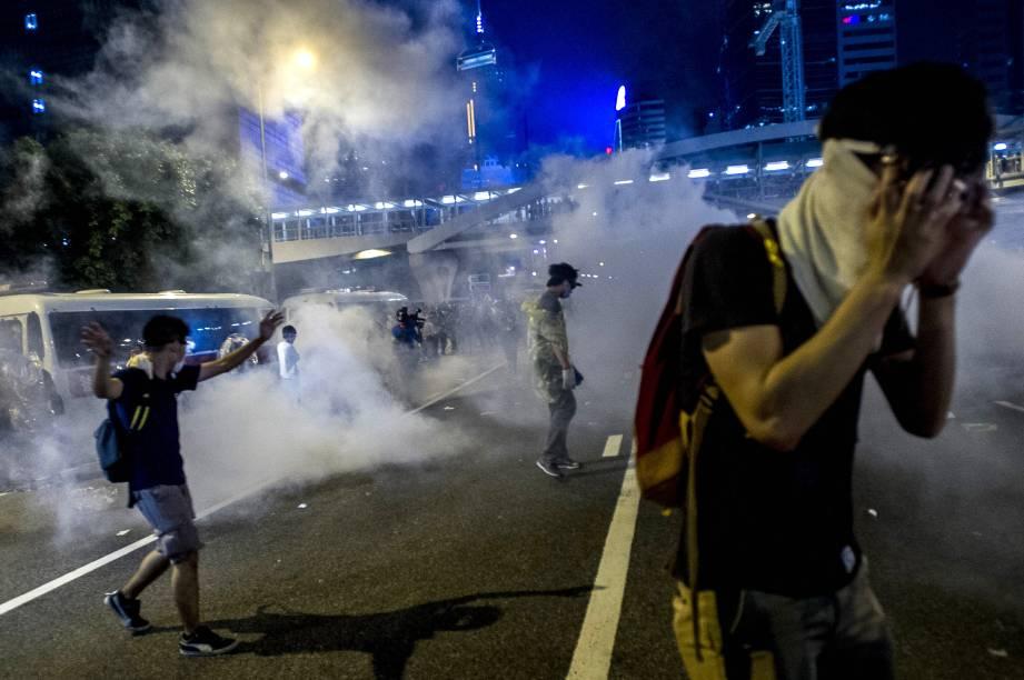 Manifestantes pró-democracia se protegem depois que a polícia usou gás lacrimogêneo para dispersar a multidão próximo a sede do governo de Hong Kong, na China