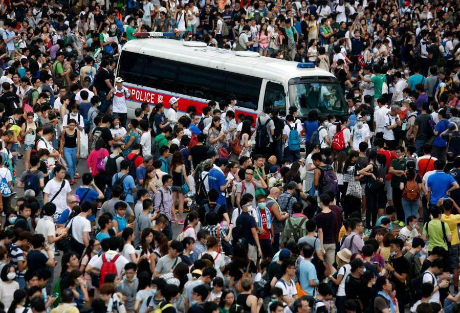 Um veículo da polícia é fotografado em meio a milhares de manifestantes pró-democracia que bloqueiam a rua principal do distrito financeiro, em frente à sede do governo de Hong Kong, na China