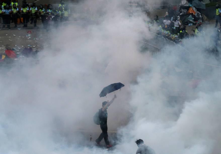 Um manifestante anda em meio à fumaça de gás lacrimogêneo disparado por policiais durante um ato pró-democracia, em frente à sede do governo de Hong Kong, na China