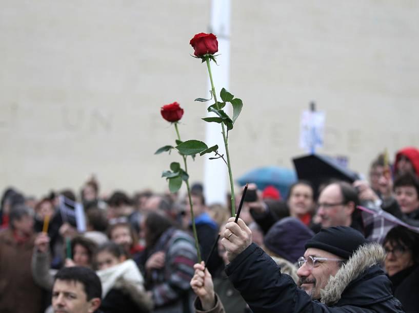 Dezenas de pessoas levam flores e lápis em um protesto na Praça do Memorial, na cidade de Caen, em memória às vítimas mortas no atentado terrorista que atingiu a França na última semana