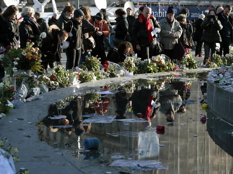 Dezenas de pessoas depositam flores e cartazes próximo a estátua de Marianne, na Praça da República, região leste de Paris, em homenagem às vítimas dos atentados terrorista que assolaram o país na última semana