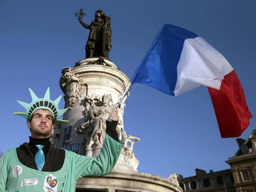 Homem vestido como a Estátua da Liberdade ergue a bandeira nacional francesa na Praça da República, em Paris, antes do início de uma grande marcha onde mais de um milhão de pessoas são esperadas além de dezenas de líderes mundiais em uma exposição histórica de desafio global contra o extremismo
