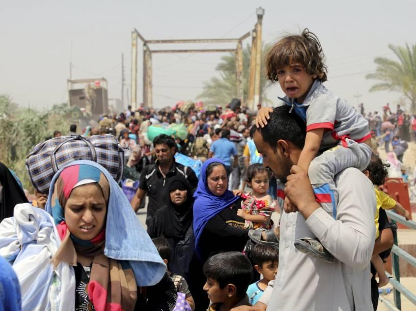 Homem desabrigado fugindo da violência em Ramadi carrega criança nas costas, próximo a Bagdá, Iraque