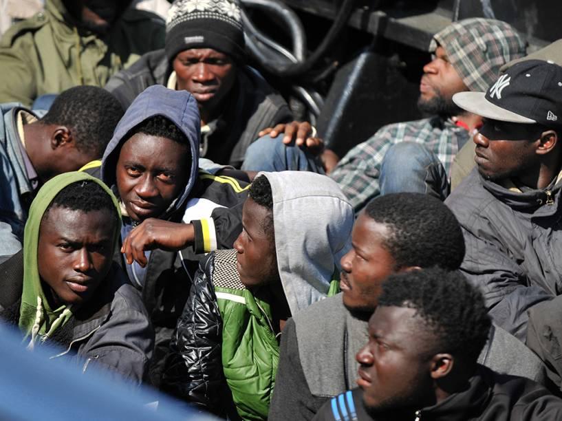 Grupo de imigrantes que sobreviveram a naufrágio aguardam por atendimento médico no porto de Corigliano Calabro, na Itália