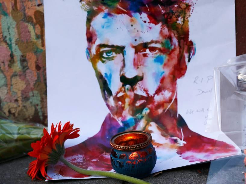 Ingleses deixam flores em frente a uma famosa pintura de David Bowie em Londres, nesta segunda-feira (11)