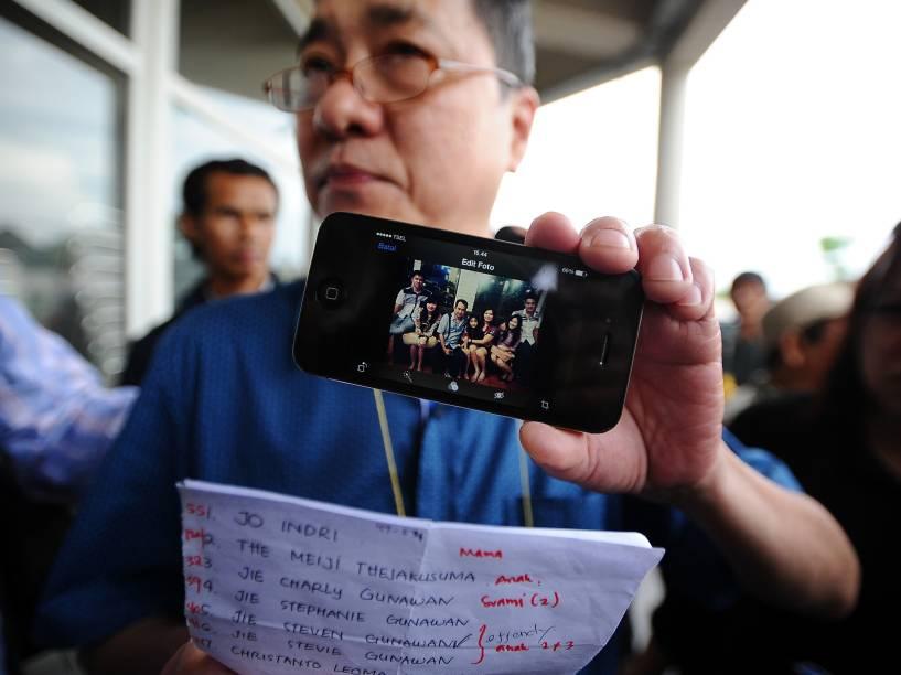 Homem exibe fotografia de seus familiares, vítimas do acidente aéreo com o voo QZ8501 da AirAsia em Surabaya, na Indonésia - 03/01/2015