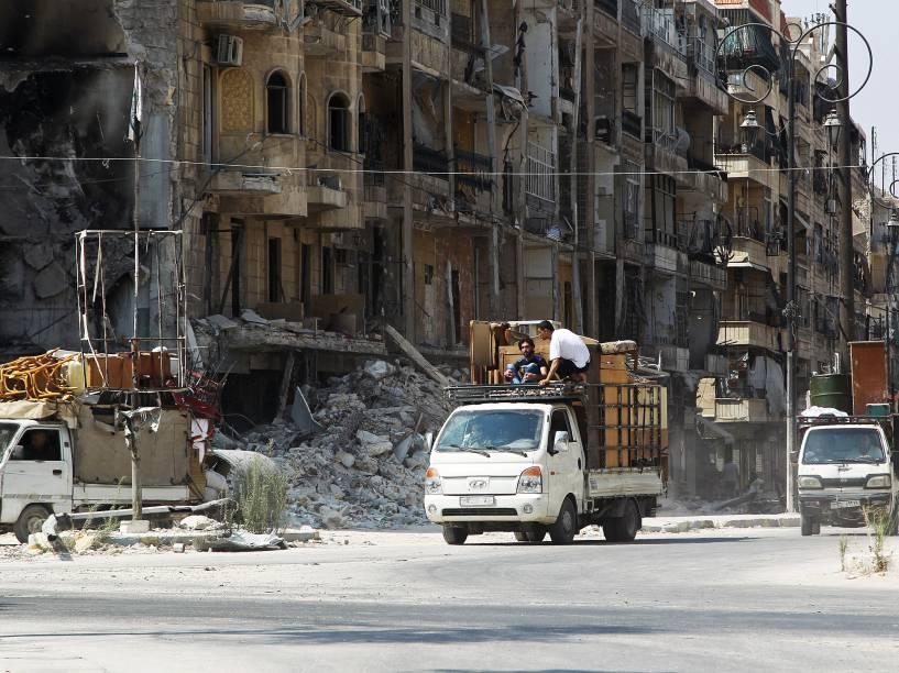 Homens carregam móveis em pequenos caminhões na cidade síria de Aleppo - 24/08/2015