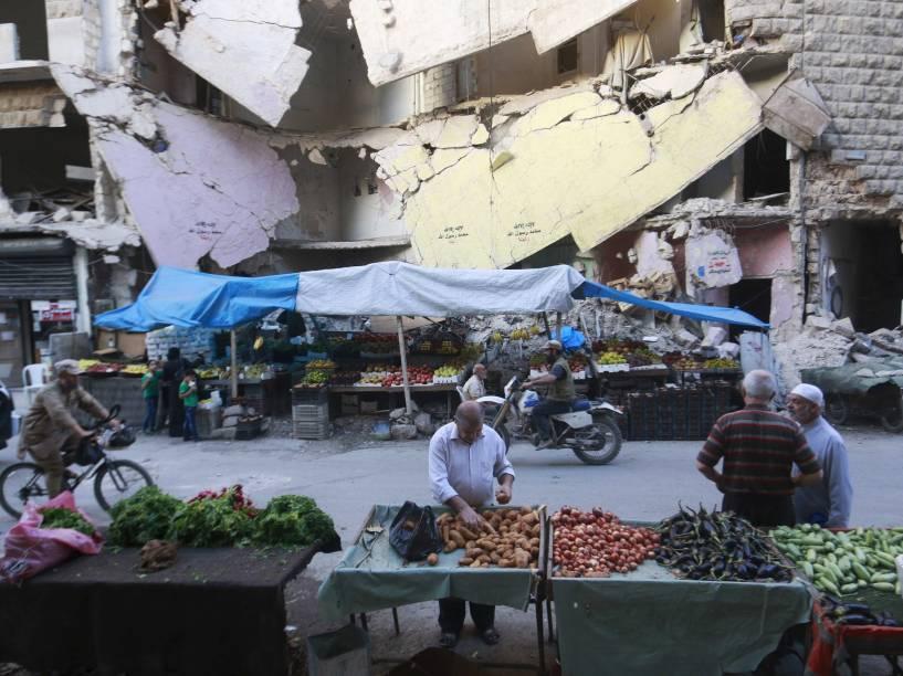 Civis compram legumes e frutas em bancas montadas em frente a edifícios danificados no bairro Bustan al-Qasr de Aleppo, na Síria - 14/10/2015