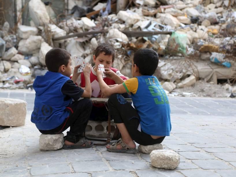 Crianças jogam cartas em meio a edifícios danificados na cidade velha de Aleppo, na Síria - 18/10/2015