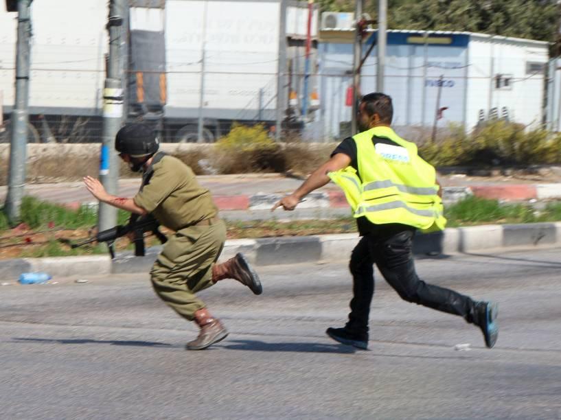 Palestino que se passava por jornalista, corre para atacar com uma faca um soldado israelense perto da cidade de Hebron, Cisjordânia