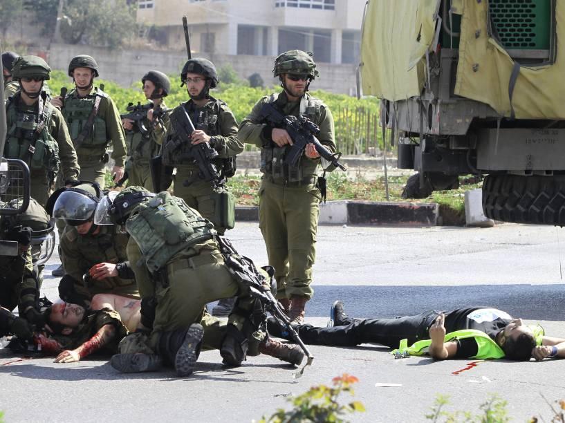 Soldados israelenses socorre o companheiro ferido ao lado do corpo do palestino agressor