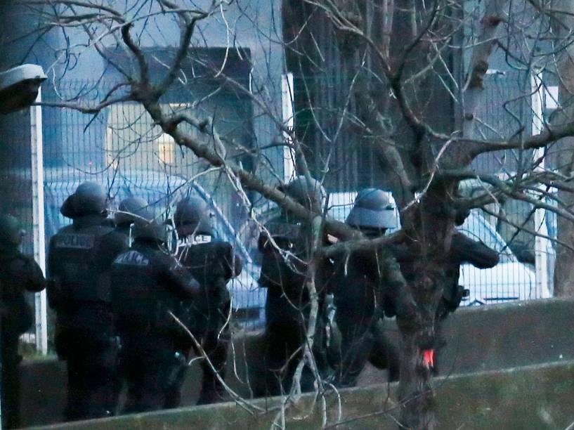 Fumaça é vista à esquerda de policiais que tentam entrar no supermercado onde várias pessoas são feitas reféns no leste de Paris
