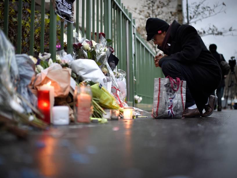Homem se ajoelha na frente de velas e flores colocadas perto dos escritórios do jornal satírico francês Charlie Hebdo em Paris - 08/01/2015