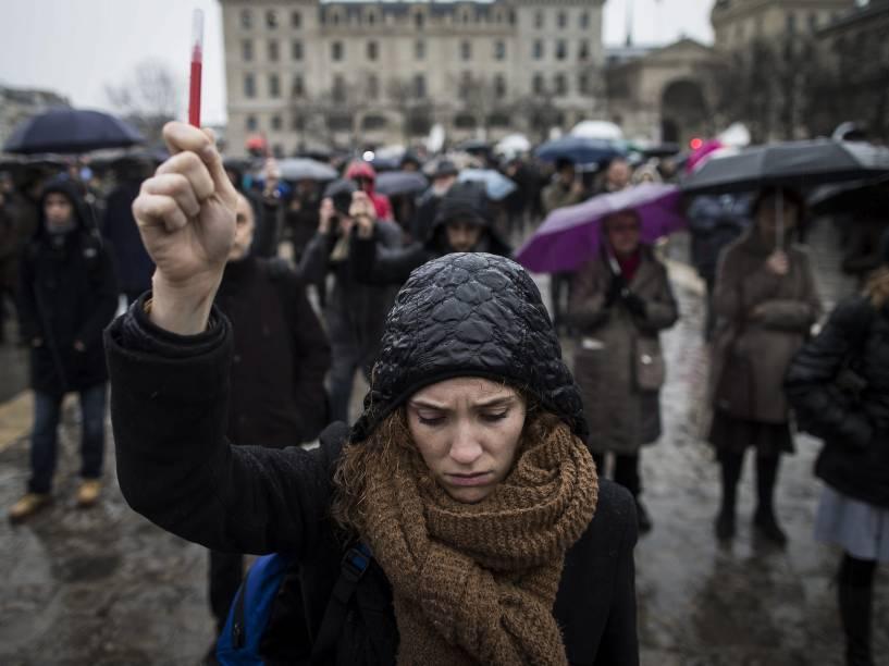 Mulher segura uma caneta durante um minuto de silêncio em frente à catedral de Notre Dame, em Paris, em memória das vítimas do ataque à redação da revista Charlie Hebdo - 08/01/2015