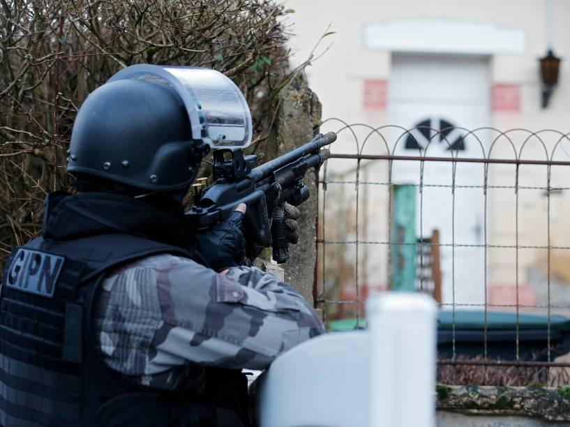 Membro da polícia francesa anti-terrorismo patrulha uma área em Corcy, a nordeste de Paris, onde os suspeitos do ataque à revista Charlie Hebdo foram vistos após roubar um posto de gasolina - 08/01/2015