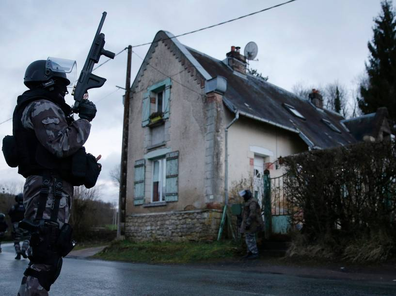 Membros da polícia francesa anti-terrorismo patrulham uma área em Corcy, a nordeste de Paris, onde os suspeitos do ataque à revista Charlie Hebdo foram vistos após roubar um posto de gasolina - 08/01/2015