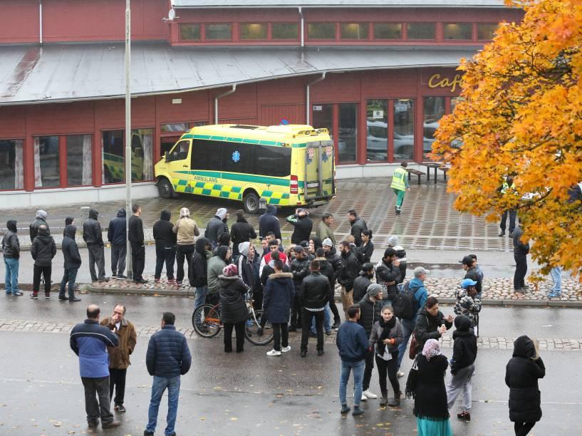 Populares se concentram nos arredores de uma escola em Trollhättan, na Suécia após o ataque de um homem mascarado armado com uma espada - 22/10/2015
