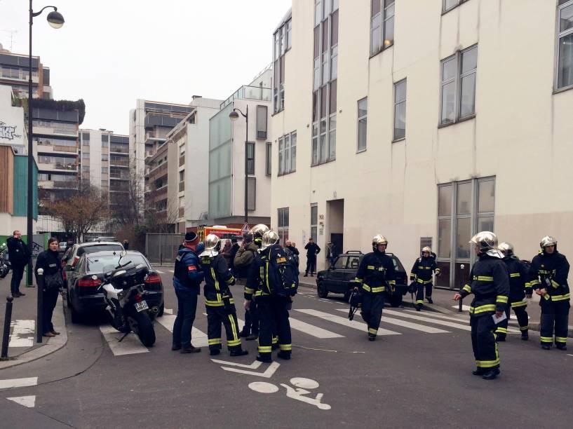 Policiais e bombeiros se reúnem em frente aos escritórios do jornal satírico francês Charlie Hebdo em Paris, depois de homens armados terem invadido o local - 07/01/2015