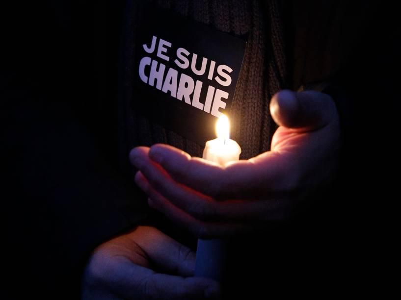 """Francês segura vela em frente a um cartaz com a mensagem """"eu sou Charlie"""", em homenagem que reúne milhares na Place de la Republique (Praça da República), em Paris, na França, depois que homens armados invadiram os escritórios da revista francesa Charlie Hebdo. Pelo menos 12 pessoas morreram durante o ataque"""