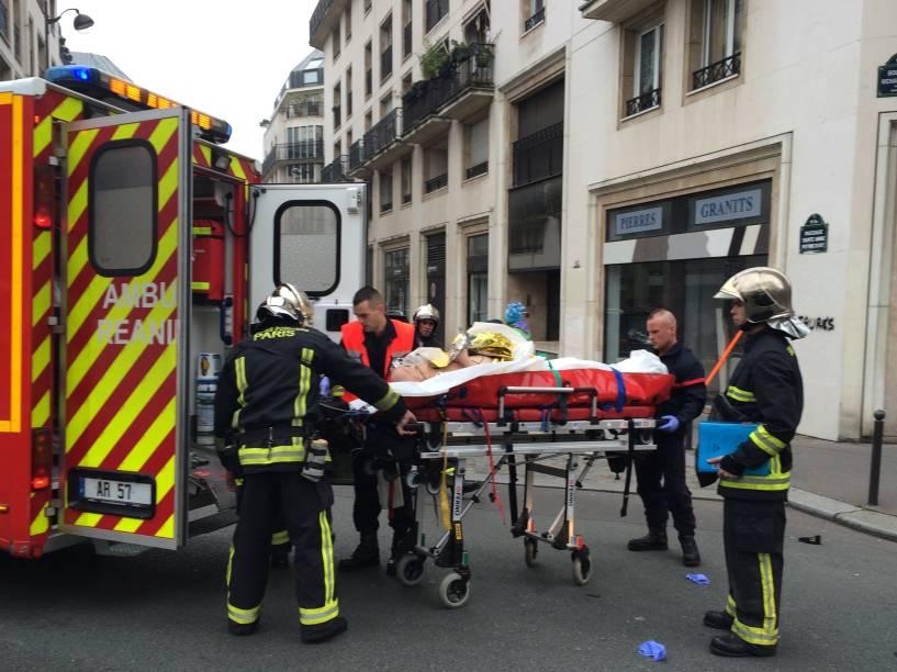 Bombeiros carregam um homem ferido em uma maca na frente dos escritórios do jornal satírico francês Charlie Hebdo em Paris, após o ataque de homens armados - 07/01/2015