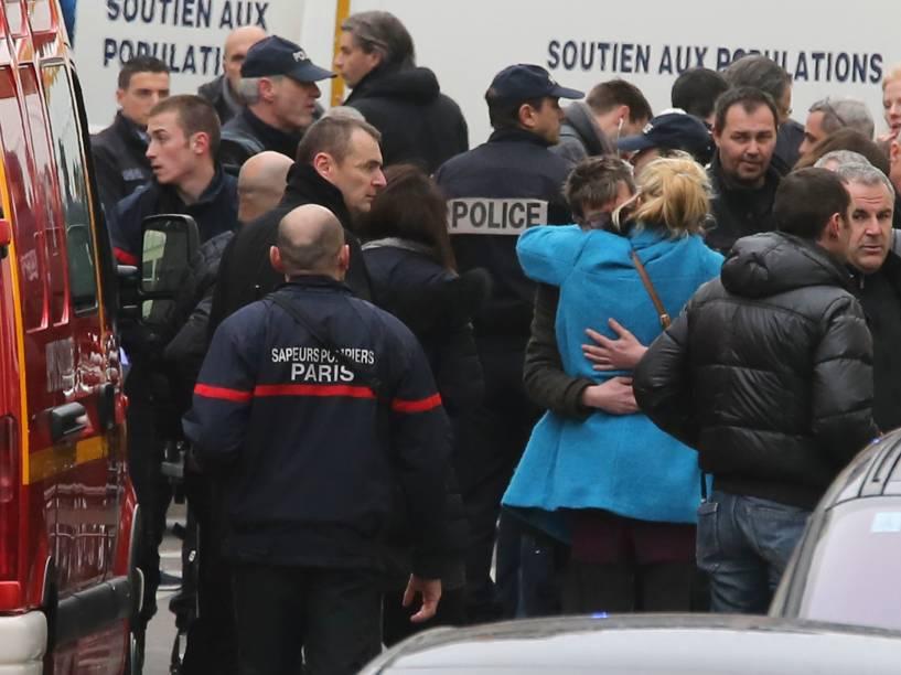 Pessoas se abraçam, depois que homens armados invadiram os escritórios da revista francesa Charlie Hebdo, em Paris. Pelo menos 12 pessoas morreram durante o ataque