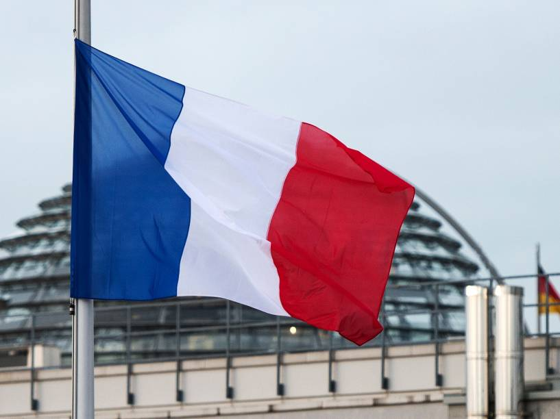A Bandeira da França fica a meio-mastro, em Berlim, depois que homens armados invadiram os escritórios da revista francesa Charlie Hebdo, em Paris. Pelo menos 12 pessoas morreram durante o ataque