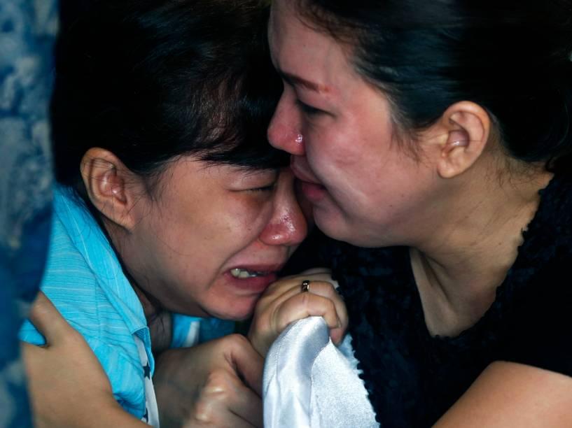 Familiares de passageiros a bordo do avião desaparecido QZ8501 da AirAsia esperam por notícias no Aeroporto Internacional de Juranda, em Surabaya, na Indonésia