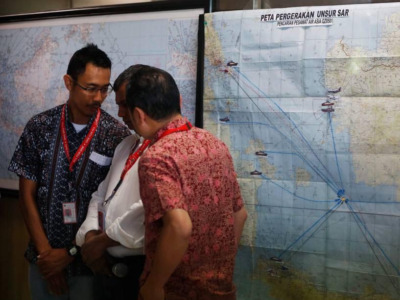 Diretores executivo da Air Asia e da Indonesia Air Asia conversam em frente a mapa para tentar encontrar o avião desaparecido na região de Surabaia, na Indonésia