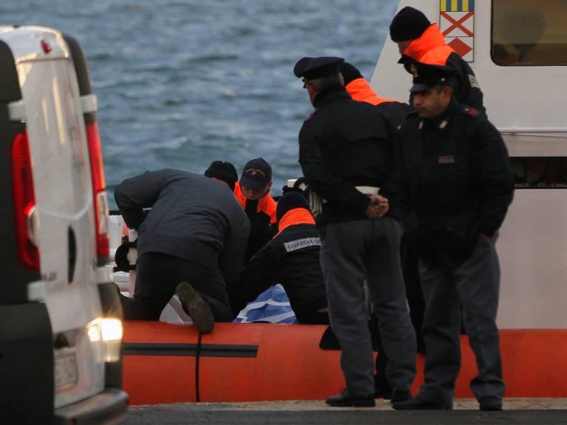 Membros da Guarda Costeira Italiana carregam corpo de passageiro da balsa Norman Atlantic ao chegarem na província de Brindisi, na Itália